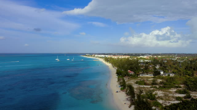 aerial: providenciales beach, people lounging under royal blue umbrellas, beachfront condominiums and sailboats in tropical water - royal blue stock videos & royalty-free footage