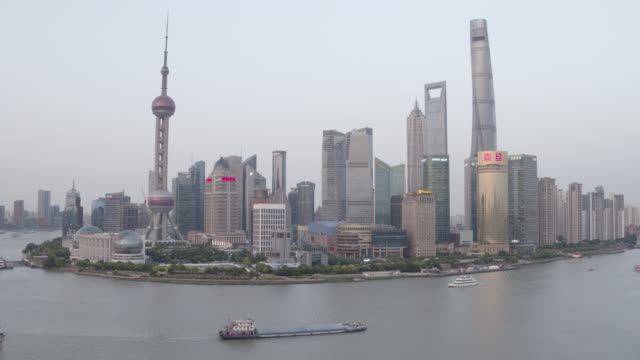 ws aerial pull back from shanghai lujiazui skyline with custom house, huangpu river, pearl tower, jin mao, world financial center, the bund - custom house tower stock videos & royalty-free footage