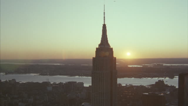 aerial pull back of empire state building and sunset in far backgrounf. pulls back to new york city skyline. hues of pink and blue along horizon in far background. beauty shot. - empire state building video stock e b–roll