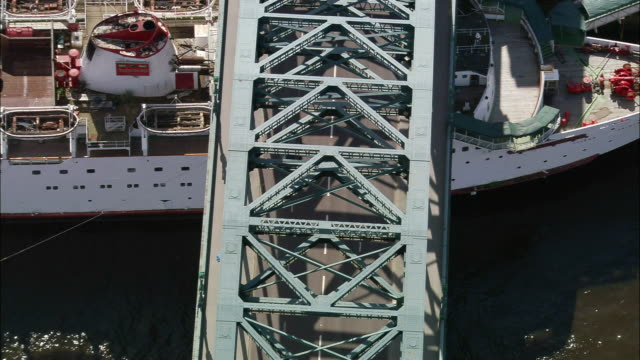 aerial pull out over tyne bridge with ships moored underneath on river tyne / newcastle upon tyne - newcastle upon tyne stock-videos und b-roll-filmmaterial