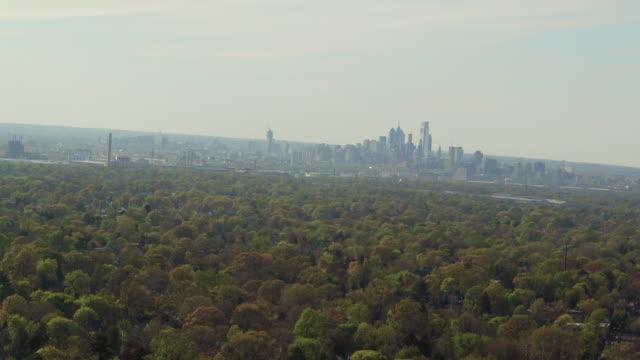 Aerial pulling away from Philadelphia skyline over lush trees