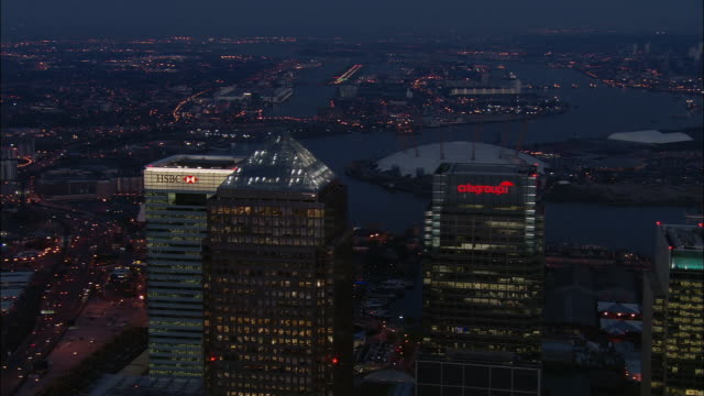 vídeos de stock e filmes b-roll de aerial pulling away from tops of skyscrapers in canary wharf at dusk / london - hsbc towers