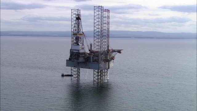 aerial pulling back from an oil rig in moray firth / highland, scotland - platform stock videos & royalty-free footage