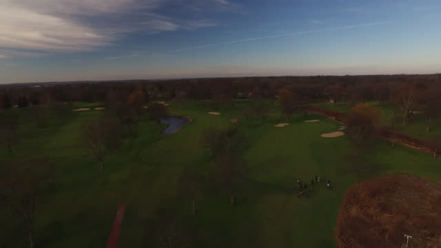 Aerial pulling back over golf course on sunny fall day