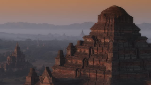 aerial push into large ancient temple at sunrise in myanmar - pagan stock-videos und b-roll-filmmaterial