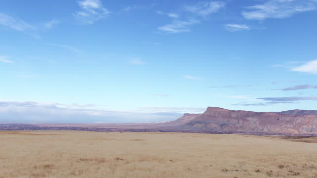 vidéos et rushes de aerial pushing out drone shot of mount garfield and the bookcliffs (rocky mountains) in the grand valley of western colorado with storm clouds on the horizon - plateau caractéristiques de la terre