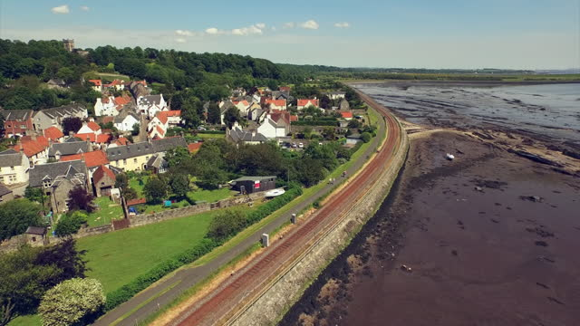 aerial: quaint village borders harbor at low tide with boats stranded in mud with nearby lush hill in sunshine - culross, scotland - sunlight stock videos & royalty-free footage