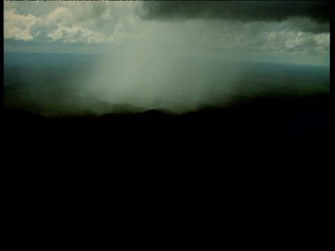 Aerial, rain pours down onto dark Amazon jungle below
