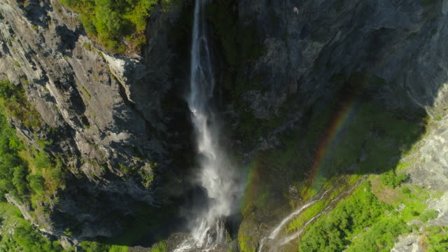 aerial: rainbow appearing over misty waterfall falling from rocky cliff during sunny day - geiranger fjord, norway - öffentlicher auftritt stock-videos und b-roll-filmmaterial