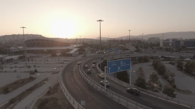 Aerial - raw footage - Athens - Piraeus - Pireas, Greece, flying above a traffic hub, bridges, tram, cable car and cars at sunset