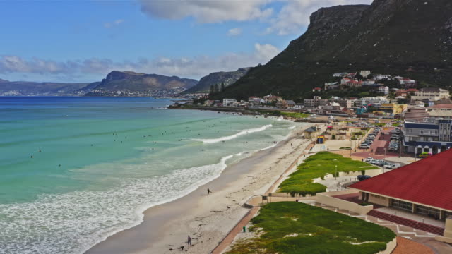 aerial real time video of people surfing at muizenberg beach - strand south africa stock videos & royalty-free footage