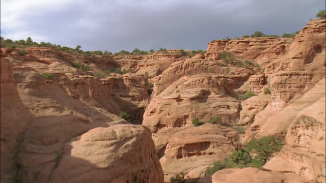 aerial rear point of view over desert terrain through canyon system / southwest usa - セージブラッシュ点の映像素材/bロール