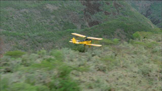 aerial rear side view of biplane flying over valley - 複葉機点の映像素材/bロール
