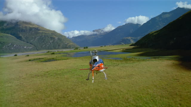 aerial rear view of helicopter flying over water in valley / new zealand - propeller stock videos & royalty-free footage