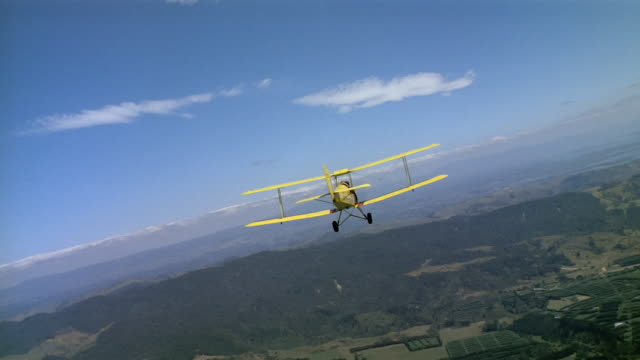 aerial rear view of yellow biplane flying over fields in valley / new zealand - 複葉機点の映像素材/bロール