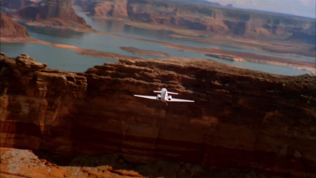 Aerial rear view private jet flying through Grand Canyon / Arizona
