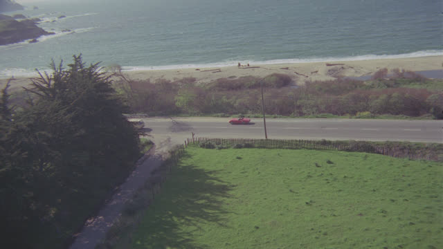 aerial red convertible on pch near carmel; turns & stops at monastery - carmel california stock videos & royalty-free footage