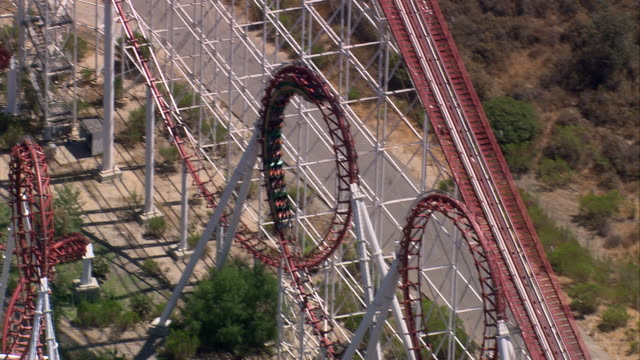 aerial ts red roller coaster in six flags theme park  / valencia, california, united states. - amusement park stock videos & royalty-free footage