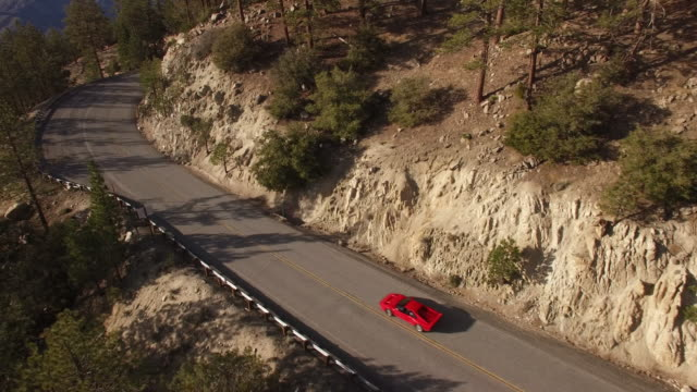 Aerial red sports car chase through forest
