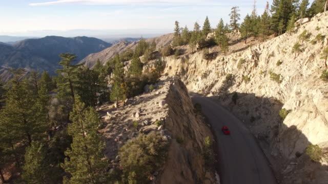 aerial roten sportwagen verfolgungsjagd durch wald - sportwagen stock-videos und b-roll-filmmaterial