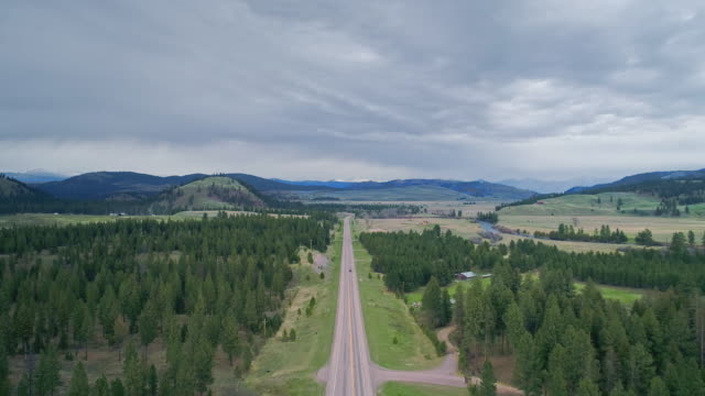 aerial remote view toward rocky mountain and lewis and clark national forest, and salmon lake state park, along the highway mt 200 near greenough, montana, in early spring.  drone video with the backward camera motion. - pick up truck stock videos & royalty-free footage