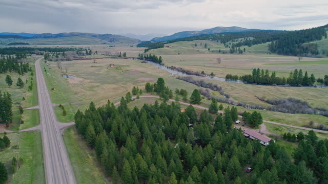 vídeos de stock e filmes b-roll de aerial remote view toward rocky mountain and lewis and clark national forest, and salmon lake state park, along the highway mt 200 near greenough, montana, in early spring.  drone video with the panoramic camera motion. - montana