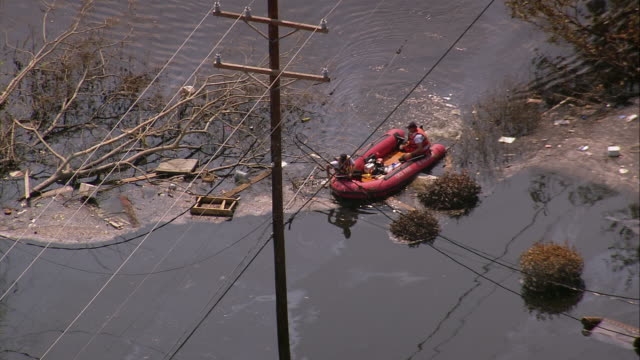 aerial rescuers in dinghy steering around debris in flooded gentilly subdivision / new orleans low angle - 2005 stock videos & royalty-free footage