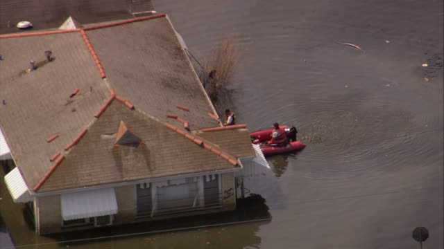aerial rescuers in inflatable dinghy marking house in flooded gentilly subdivision / new orleans low angle - hurricane katrina stock videos and b-roll footage