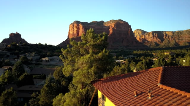 aerial reveal of rock formation in sedona, az at sunset - arizona stock-videos und b-roll-filmmaterial
