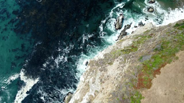 aerial reveal shot of the bixby bridge and highway 1 by the cliffs and shoreline in monterey california - klippe stock-videos und b-roll-filmmaterial