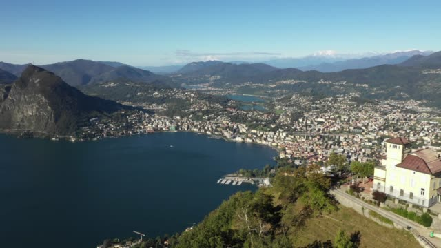 vídeos de stock e filmes b-roll de aerial revealing shot of city by a lake with mountains - switzerland