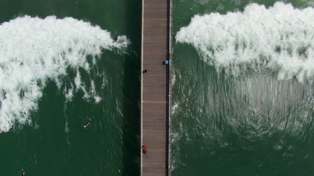 aerial reverse flyover of the pacific beach pier with a slight tilt down towards crashing waves, surfers, and kelp - san diego, california - aerial stock videos & royalty-free footage