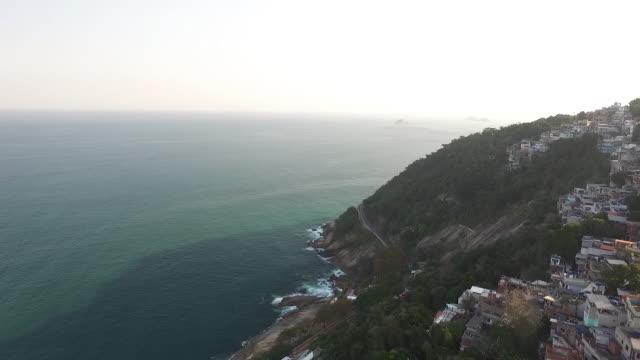 aerial reverse of rio de janeiro coastal town - favela stock videos and b-roll footage