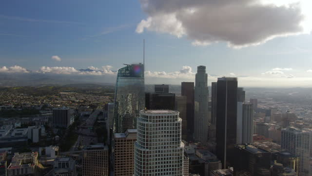 aerial reverse shot of the wilshire grand center high-rise and neighboring buildings reflected in the windows all set against a sunny, blue sky and hill stretching to the horizon - amazing aerials of building clos - los angeles, california - majestic stock videos & royalty-free footage