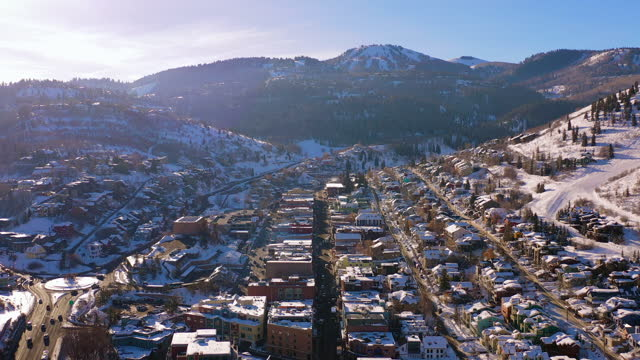 aerial reversing above residential neighborhood in a snowy mountain ski town with quiet streets and bright morning sunlight - park city, utah - park city stock videos & royalty-free footage