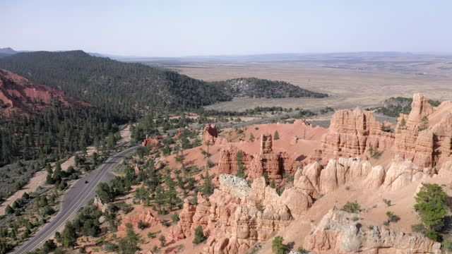 aerial reversing away from vast plains and backing into a canyon, with bright sunlight, hoodoos, blue sky, pine trees, and the rolling hills stretching to the horizon - bryce, utah - ブライス峡谷点の映像素材/bロール