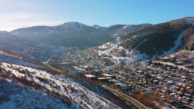 aerial reversing high above residential neighborhood in a snowy mountain ski town with quiet streets and bright morning sunlight - park city, utah - park city stock videos & royalty-free footage