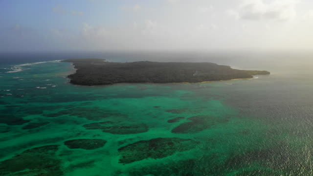 aerial right: forest covered island surrounded by vibrant blue ocean - little corn island, nicaragua - nicaragua stock videos & royalty-free footage