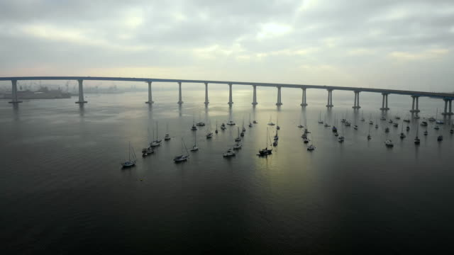 stockvideo's en b-roll-footage met aerial right, pan left: boats floating in ocean by long bridge into city in san diego, united states of america - san diego