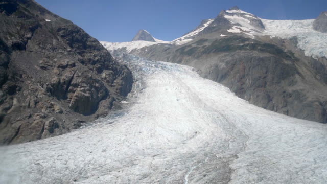 aerial right: snow covered, rocky valley surrounded by gray, snowy mountains - mendenhall glacier, alaska - tall high stock videos & royalty-free footage