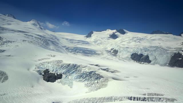 vídeos de stock, filmes e b-roll de aerial right: snowy valley and mountains with bright, blue sky above - mendenhall glacier, alaska - alto descrição geral