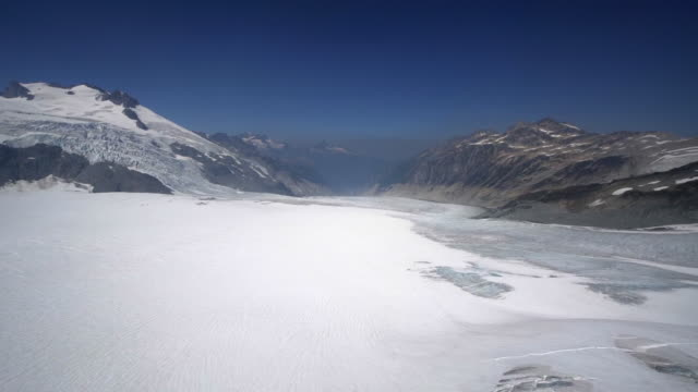 aerial right: snowy valley surrounded by mountains, foggy, blue sky above - mendenhall glacier, alaska - アラスカ点の映像素材/bロール