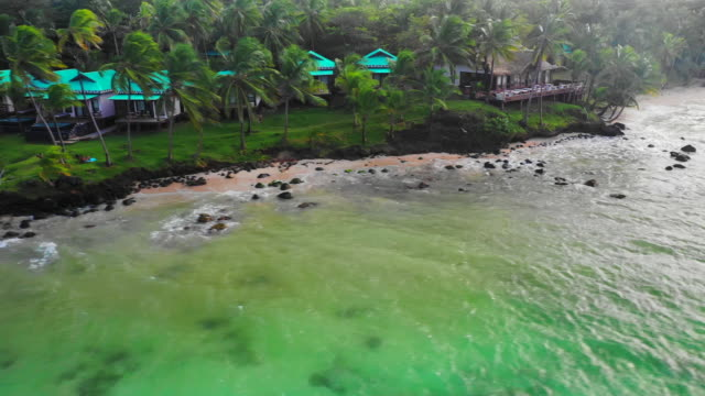 aerial right/pan left: buildings on shore of forest by vibrant green ocean - little corn island, nicaragua - tropischer baum stock-videos und b-roll-filmmaterial