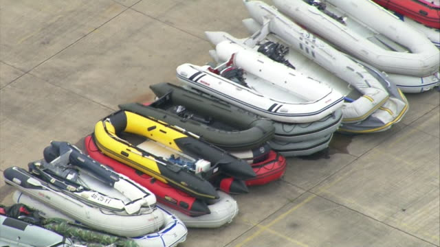 aerial rigid inflatable boats used by illegal migrants to cross the english channel piled up and stored at port in kent - stack stock videos & royalty-free footage