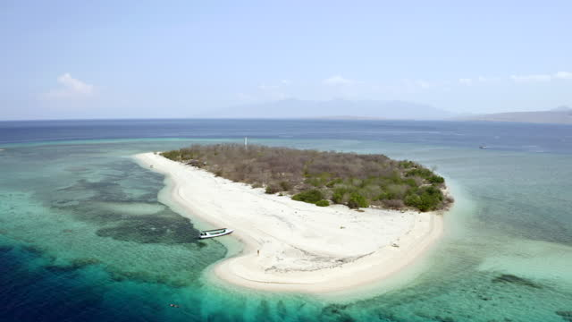aerial rising above a boat on the beach of a small coral reef island surrounded by shimmering deep blue ocean extending to the horizon - east java, indonesia - coral stock videos & royalty-free footage