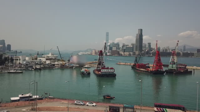 aerial: rising above a motorway and overpass to show victoria harbor in hong kong - anchored stock videos & royalty-free footage