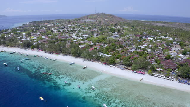 aerial rising above the shoreline of a coral reef island, with deep blue see and small boats anchored nearby - gili, indonesia - anchored bildbanksvideor och videomaterial från bakom kulisserna