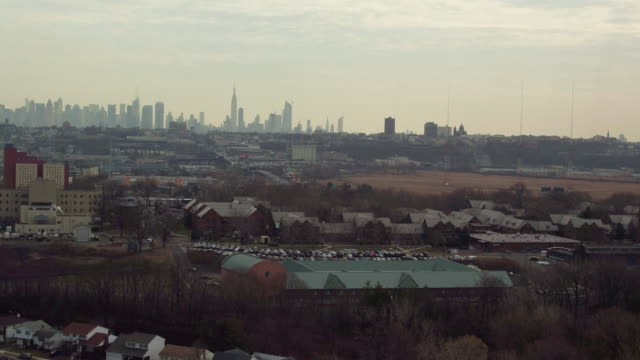 Aerial rising and falling over industrial suburb with New York City on the horizon