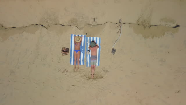 Aerial Rising: Couple Sunbathing on the Beach