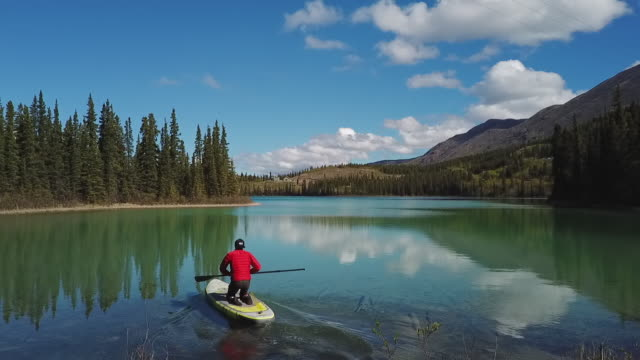 vidéos et rushes de aerial rising: launching stand-up paddleboard at emerald lake of canada - canoë